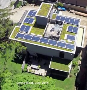 Aerial View of residential home with green roof and solar panels.