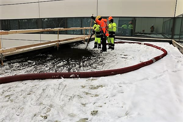Two installers on rooftop installing growing media on a snowy wintery day.